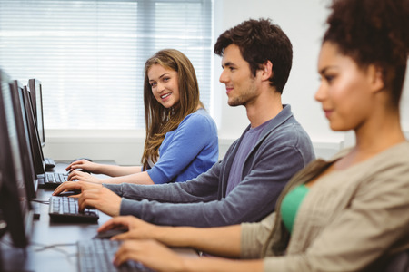 Happy student in computer class smiling at camera at the university photo