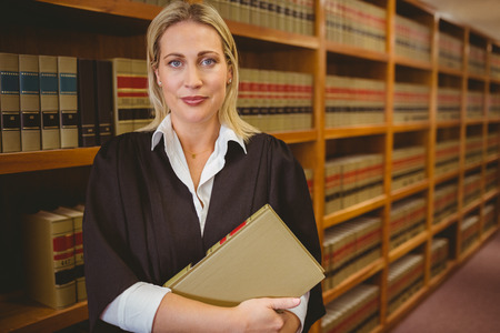 female lawyer: Serious lawyer holding a file while standing in library Stock Photo