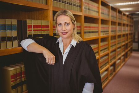law school: Smiling lawyer leaning on shelf in library
