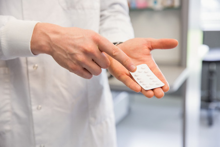 pharmaceutic: Pharmacist holding medicine blister pack at the hospital pharmacy