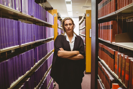 unsmiling: Unsmiling lawyer standing between shelfs with arms crossed in library