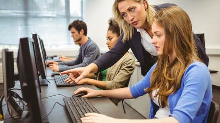 usando computadora: Profesor atractivo ayudando a su estudiante en la clase de computación en la universidad Foto de archivo