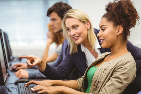 college classroom: Attractive teacher talking to her student in computer class at the university Stock Photo