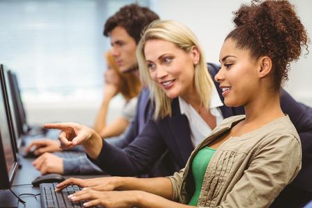 Profesor atractiva que habla a su alumno en clase de computación en la universidad Foto de archivo - 36403997
