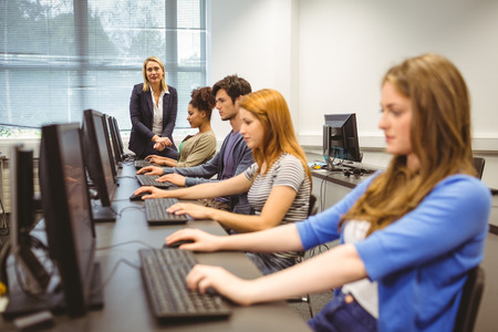 Four focused students with teacher at the end of the class at the university Stock Photo