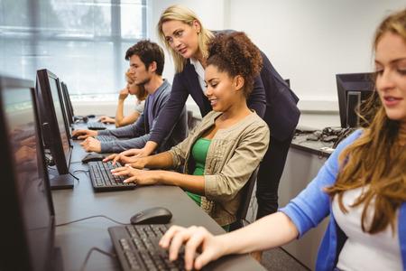 образование: Привлекательный учитель помогает ей студента в компьютерном классе в университете Фото со стока