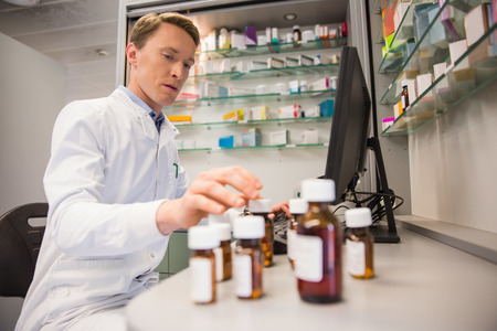 pharmacy pills: Pharmacist using computer at desk at the hospital pharmacy Stock Photo