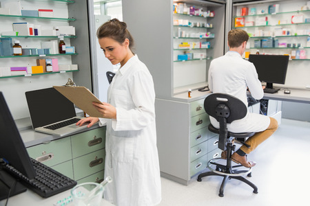 pharmacist: Team of pharmacists working on computers at the hospital pharmacy
