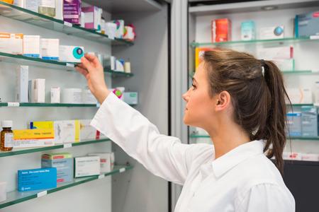 Farmacéutico Júnior tomar el medicamento de estantería en la farmacia del hospital