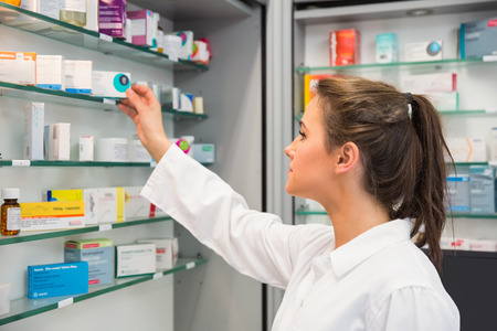 Junior pharmacist taking medicine from shelf at the hospital pharmacy Archivio Fotografico