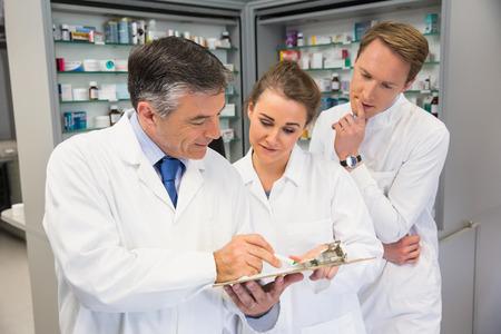 farmacia: Personas de farmac�uticos que mira el sujetapapeles en la farmacia del hospital Foto de archivo