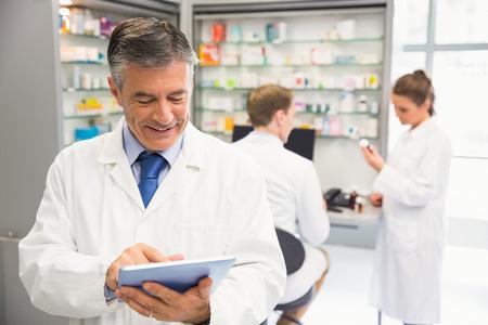 Senior pharmacist using tablet pc at the hospital pharmacy