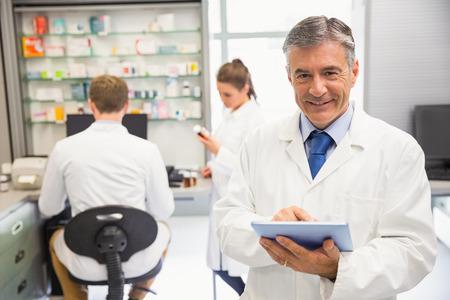 Senior pharmacist using tablet pc at the hospital pharmacy photo