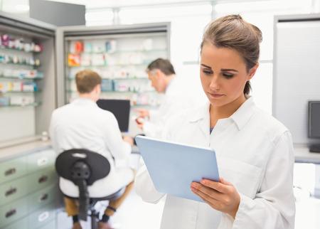 Junior pharmacist using tablet pc at the hospital pharmacy Stockfoto