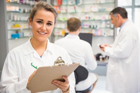 bata de laboratorio: Farmac�utico J�nior escrito en el portapapeles en la farmacia del hospital