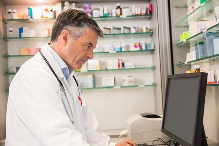 farmacia: Farmac�utico Focused usando la computadora en la farmacia del hospital