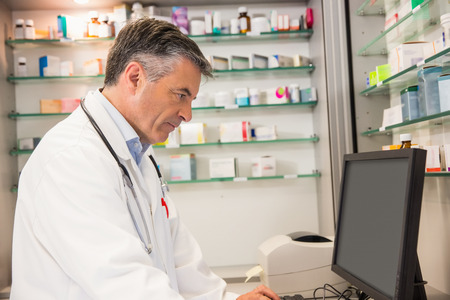 Focused pharmacist using the computer at the hospital pharmacy