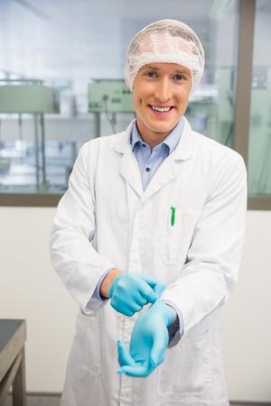 rubber gloves: Pharmacist pulling on rubber gloves at the hospital pharmacy