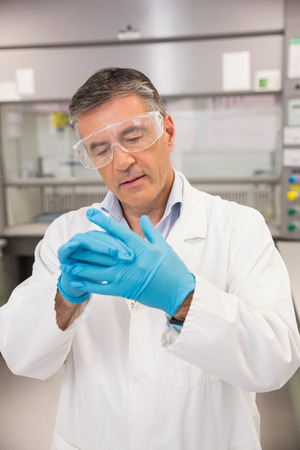 putting on: Senior pharmacist putting on his gloves at the laboratory