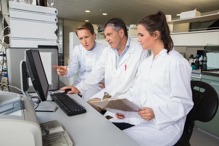 Team of scientists working together at the laboratory Imagens