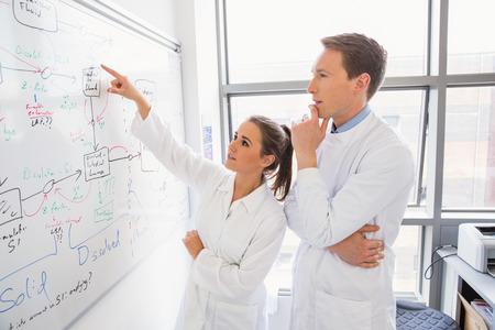 in lab: Estudiante de la ciencia y profesor mirando a la pizarra en el laboratorio