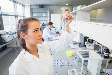 scientist man: Young scientist holding up test tube at the laboratory Stock Photo