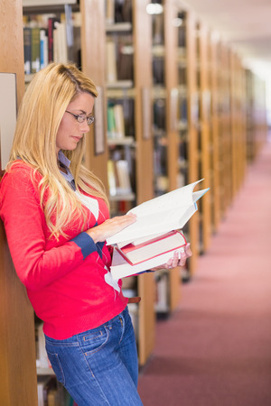 revision book: Mature student reading in library at the university Stock Photo