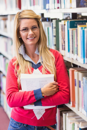 female student: Mature student in library smiling at camera at the university Stock Photo