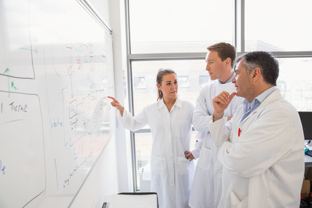 bata de laboratorio: Los estudiantes de ciencias y profesor mirando de pizarra en el laboratorio