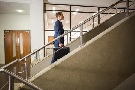 escalera: Empresario subiendo por las escaleras en el edificio de oficinas