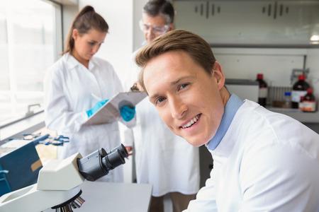 bata de laboratorio: Cient�fico que mira a trav�s de un microscopio en el laboratorio