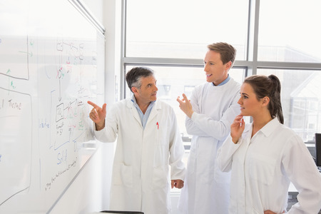Science students and lecturer looking at whiteboard at the laboratory Stock Photo