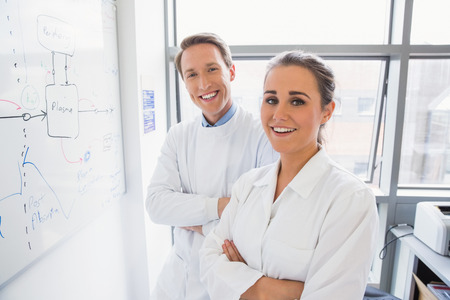 lecturer: Science student and lecturer smiling at camera at the laboratory