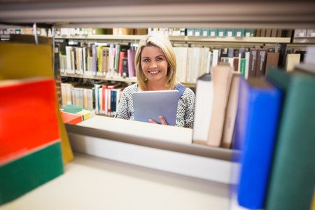 mature student: Mature student smiling in library at the university