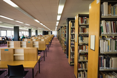 Volumes of books on bookshelf in library at the university 에디토리얼