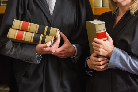 law school: Lawyers holding books in the law library at the university