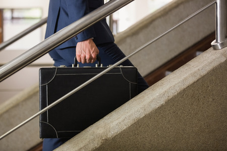 upstairs: Businessman climbing up the stairs in office building