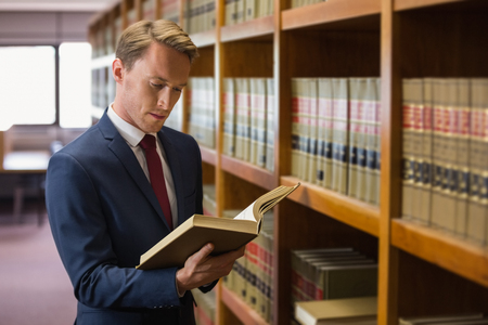 Handsome lawyer in the law library at the university Foto de archivo