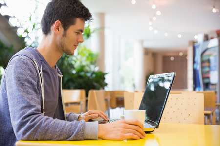 internet cafe: Estudiante joven que usa su computadora port�til en caf� en la universidad