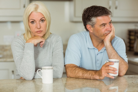 not talking: Mature couple having coffee together not talking at home in the kitchen Stock Photo
