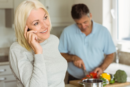 Happy mature blonde on the phone at home in the kitchen Stock Photo