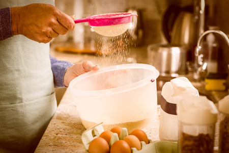 domiciles: Woman sieving flour into bowl at home in the kitchen Stock Photo