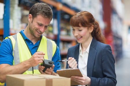 female boss: Portrait of manual worker and manager scanning package in the warehouse