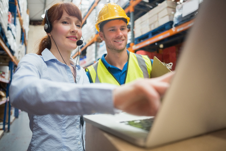 inventario: Sonriente mujer de negocios el uso de auriculares con ordenador port�til en almac�n