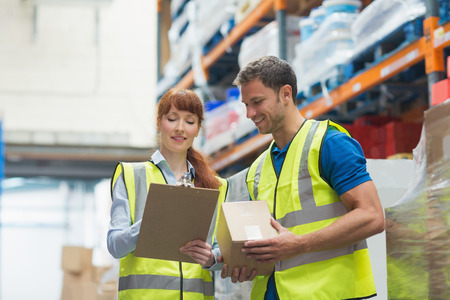 female worker: Smiling warehouse manager and delivery man in warehouse