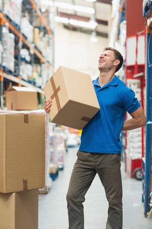 dolor de espalda: Vista lateral del trabajador con el dolor de espalda, mientras que la caja de elevaci�n en el almac�n