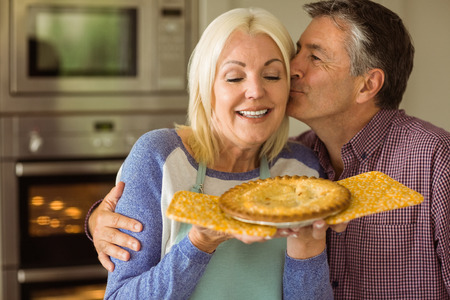 hot love: Mature blonde holding fresh pie with husband kissing her at home in the kitchen Stock Photo