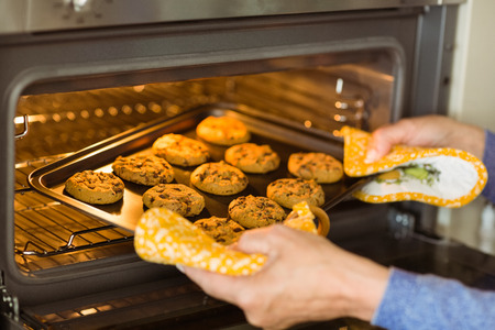 baking tray: Woman taking tray of fresh cookies out of oven at home in the kitchen