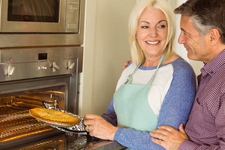 taking a wife: Woman taking fresh pie out of oven with husband at home in the kitchen Stock Photo