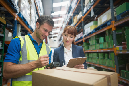 woman boss: Portrait of manual worker and manager scanning package in the warehouse